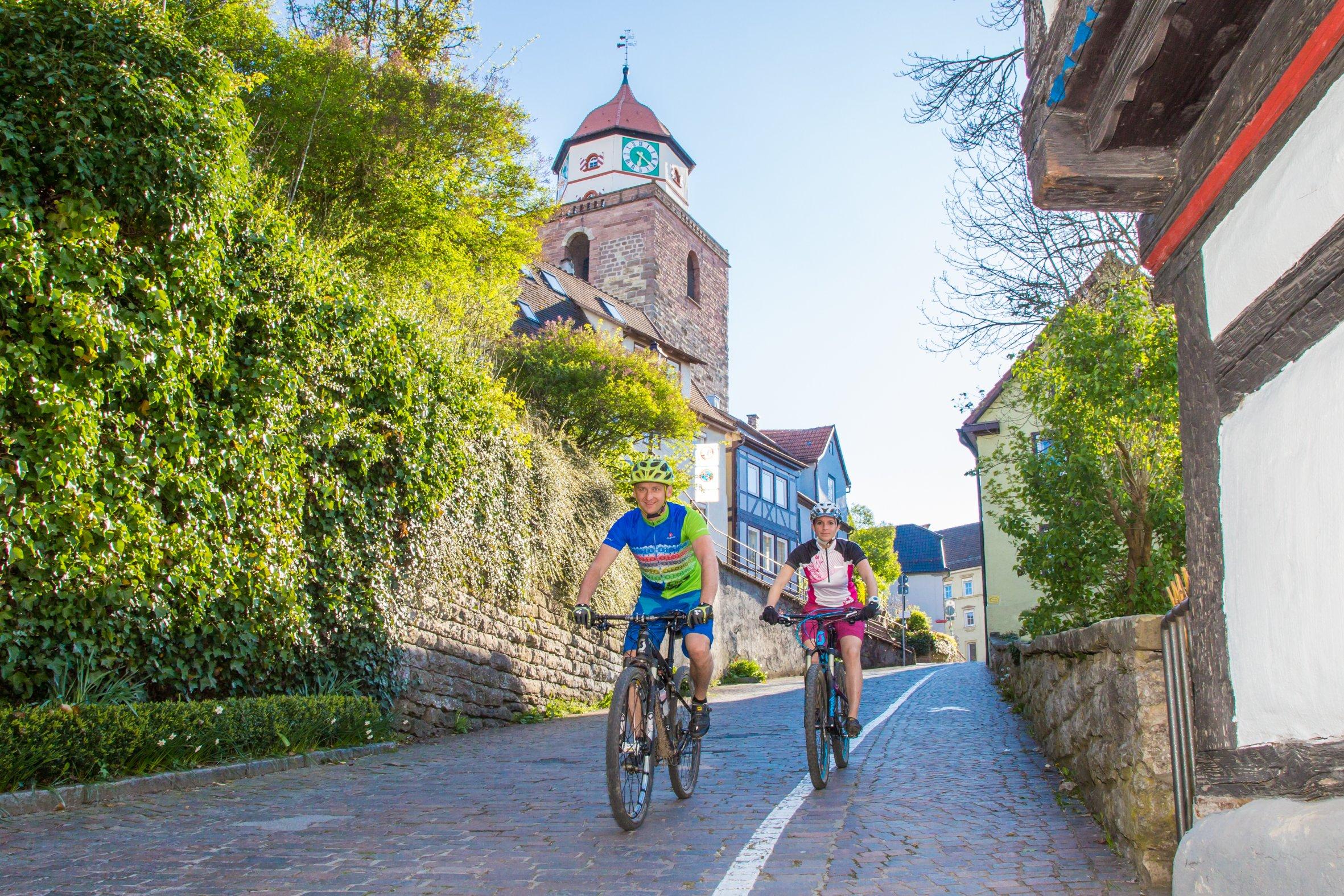 Zwei Radfahrer im Hintergrund das Wahrzeichen von Haigerloch der Römerturm