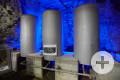Drei große, graue Wassertanks vor blau angeleuchteter Felswand im Atomkeller-Museum