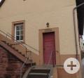 Hausausschnitt mit roter Haustür und einem Fenster. Eine Treppe führt von unten zur Haustüre und weiter nach oben.