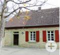 Steinhaus mit einer Tür und 2 Fenstern mit roten Holzfensterläden. Eingerahmt von einem herbstlichen Baum, mit wenig Blättern.