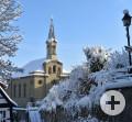 Kirche eingerahmt in eine Winterlandschaft. Links Baumäste, Rechts Gebüsch und eine Straßenlaterne