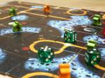 Spielfeld bestehend aus mehrern quadratischen Kärtchen. Darauf drei grüne Würfel und mehrer Spielfiguren (Meeple) in grün und orange.