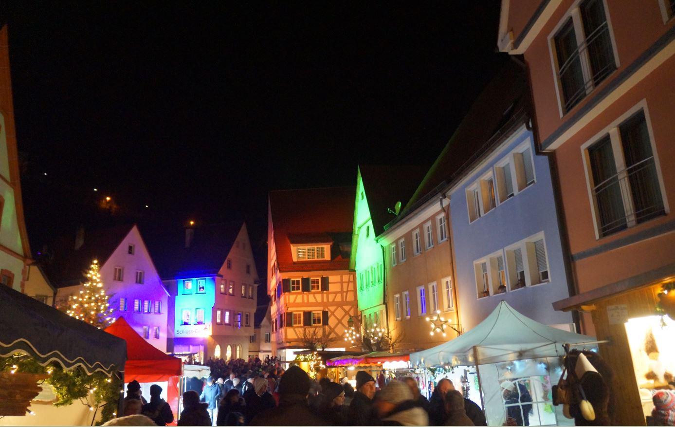Farbig beleuchtete Häuser in der gut besuchten Unterstadt bei Nacht