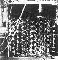 Historisches Bild des Uranreaktors mit hunderten, nach unten hängenden Ketten mit UranwürfelnUran